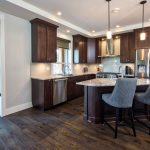 custom kitchen has island and stainless appliances