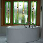 bathroom renovation by Copper Ridge Homes with modern tub and stained glass window