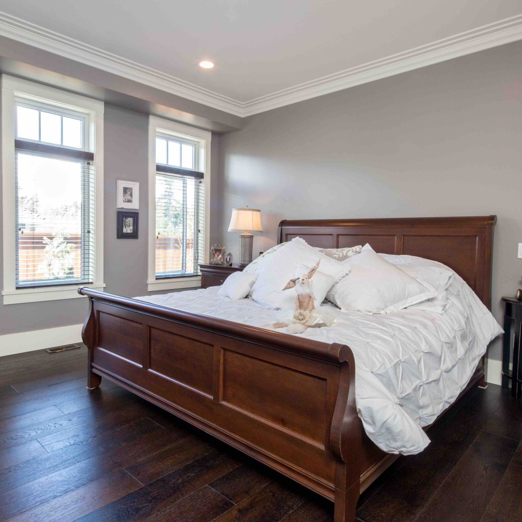 large sleigh bed in master bedroom of luxury home